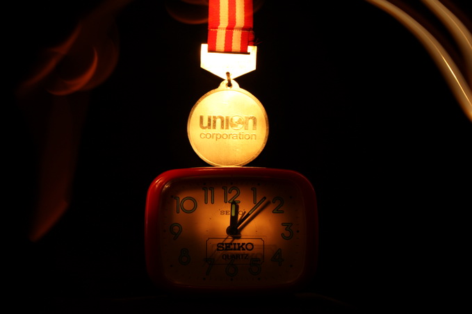 Lighted by a single flashlight on the medal and the clock then from behind those objects